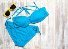 Endecha plana de los artículos del verano con el bikini y los accesorios coloridos en el fondo de madera blanco, concepto del ver imagen de archivo libre de regalías