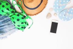 Endecha plana de los artículos y del teléfono elegante, concepto de la playa del verano en el fondo blanco imagen de archivo