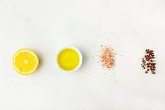 Endecha plana de los ingredientes para la salsa de la vinagreta Limón, aceite de oliva, pimienta blanca negra roja de la sal Hima imágenes de archivo libres de regalías