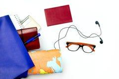 Endecha plana de un bolso y de los accesorios del ` s de la mujer con los vidrios, el mapa, el cuaderno, los auriculares y el pas Foto de archivo