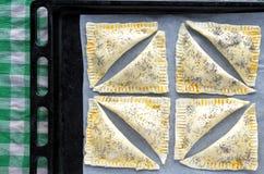 Endecha plana de una bandeja por completo con listo para ser cocinero Triangular Burekas Imagen de archivo libre de regalías
