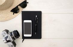 Endecha plana del concepto del viaje con la libreta y las gafas de sol, en la madera blanca fotografía de archivo