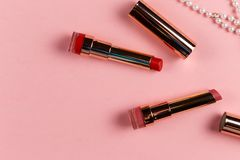Endecha plana del cosm?tico femenino creativo para la barra de labios en el fondo rosado colorido con el espacio de la copia fotos de archivo libres de regalías