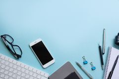 Endecha plana del negocio: escritorio con el ordenador portátil, cuaderno, lápiz, teléfono, vidrios en fondo azul Copie el espaci fotos de archivo