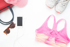 Endecha plana del teléfono móvil con los accesorios rosados del sujetador y de la mujer del deporte Fotografía de archivo libre de regalías