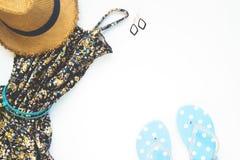 Endecha plana del vestido de la mujer con los accesorios y las sandalias en el fondo, la belleza y los artículos blancos de la pl Imagen de archivo