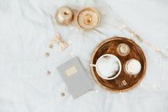 Endecha plana en cama con el café, cuaderno, accesorios de la mujer del oro Foto de archivo