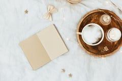 Endecha plana en cama con el café, cuaderno, accesorios de la mujer del oro Fotos de archivo libres de regalías