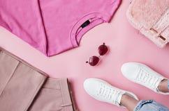 Endecha plana tirada de la ropa femenina del rosa en colores pastel con los pies Fotografía de archivo libre de regalías