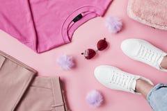 Endecha plana tirada de la ropa femenina del rosa en colores pastel con los pies Fotos de archivo