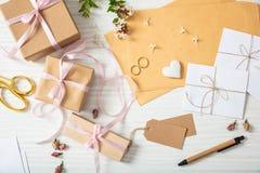 Endecha plana y vista superior de presentes y de invitaciones de la boda en un tablero de la mesa de madera blanco, fondo imagen de archivo libre de regalías