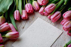 Endecha rosada aleatoriamente dispersada en una textura de madera, sobre de los tulipanes de Kraft Foto de archivo libre de regalías