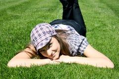 Endechas sonrientes de la muchacha en la hierba foto de archivo libre de regalías