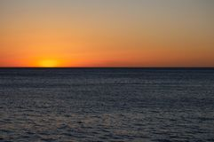 An Ending Ocean Sunset. A very low sunset over the Pacific Ocean Royalty Free Stock Photos