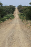 Endless African road. Dusty african road, seemingly endless, with car Royalty Free Stock Image