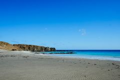 endless beautiful sandy beach shore next tu the crystal clear blue sea in the middle of the arid landscape stock photo