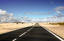 Endless coastal road and sand. Fuerteventura, coastal road through natural reserve dunes of Corralejo and beautiful cloudy sky Stock Photography