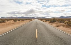 Endless Desert Highway Westbound. Street straight to the horizon in the west. California high desert January 2016 Royalty Free Stock Image