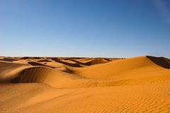 Endless desert under fair sky Stock Images