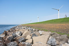 Endless dike with windmills and lonely bicycle Stock Image