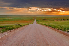 Endless Dirt Road on Prairie. Endless dirt road heading off into the distance leading to dramatic sunset sky Royalty Free Stock Photography