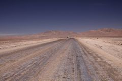 Endless dirt road to infinity of salt flat plateau contrasting with blue cloudless sky. royalty free stock photo