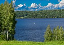 Endless expanses along the Volga river. Summer Sunny day, blue water, green shores and blue sky with white clouds floating on it Stock Photos