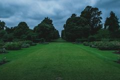 Endless Fairway of Lawns at Kew Gardens. A strong perspective of deep green lawns at Kew Gardens. The ominous grey clouds give a spooky, oppressive mood to the royalty free stock photo