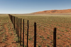 Endless fence in desert landscape Royalty Free Stock Photos