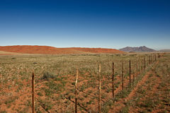 Endless fence in desert landscape Stock Image