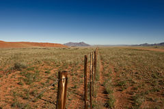Endless fence in desert landscape Stock Photography