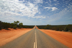 Endless Highway in Outback. Typical Australian road with red dirt by the roadside Stock Images