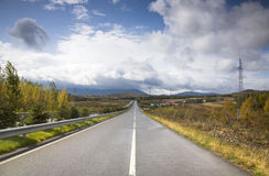 Endless highway under cloudy sky Stock Images