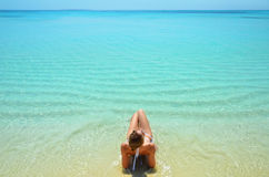 Endless lagoon. The girl takes a sun bath in the turquoise lagoon in the Maldives royalty free stock photography
