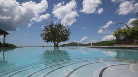 Endless Pool Tropical Island. Luxury beach resort with endless pool and clouds passing by on an tropical island stock video footage