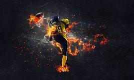 Endless power and energy. Rugby player in fire flames on dark background royalty free stock images
