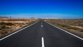 Endless road against blue sky. Endless road against a blue sky, disappears behind the horizon Stock Photo
