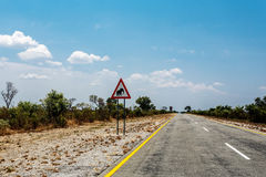 Endless road with blue sky and sign elephants crossing. In Namibia, Caprivi Game Park, with blue sky Royalty Free Stock Photography