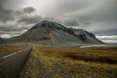Endless road at the coast with mountain stock photo