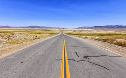 Endless road in the desert, USA. View of road among desert and mountains, California, USA Stock Photo