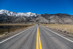 Endless road with snowed mountains in the background. California royalty free stock photos