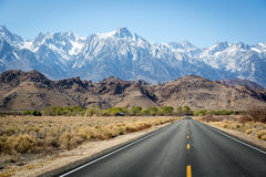 Endless road with snowed mountains in the background. California royalty free stock photography