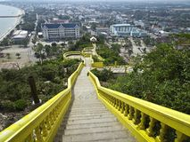 Endless staircase to the Buddhist temple in Prachuap Khiri Khan in Thailand. yellow staircase royalty free stock image