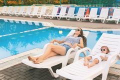 Endless summer. Cute baby and mother relaxing at sunbed. Near pool at resort. A little girl wearing sunglasses. Child and mom sunbathe. Fashion girls, friends Stock Images