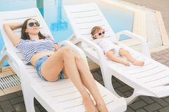 Endless summer. Cute baby and mother relaxing at sunbed. Near pool at resort. A little girl wearing sunglasses. Child and mom sunbathe. Fashion girls, friends Stock Photography