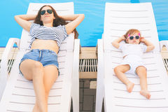 Endless summer! Cute baby and mother relaxing at sunbed. Near pool at resort. A little girl wearing sunglasses. Child and mom sunbathe. Fashion girls, friends Stock Image