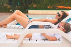Endless summer Cute baby and mother relaxing at sunbed. Near pool at resort. A little girl wearing sunglasses. Child and mom sunbathe. Fashion girls, friends Royalty Free Stock Photos