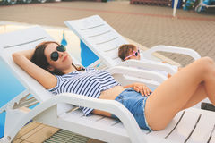 Endless summer Cute baby and mother relaxing at sunbed. Near pool at resort. A little girl wearing sunglasses. Child and mom sunbathe. Fashion girls, friends Royalty Free Stock Photo