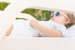 Cute baby relaxing at sunbed near pool at hawaii, hotel. Endless summer. Cute baby relaxing at sunbed near pool at hawaii, hotel. Lttle girl wearing sunglasses Stock Photos