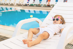 Endless summer! Cute baby relaxing at sunbed near pool, resort. Royalty Free Stock Photography